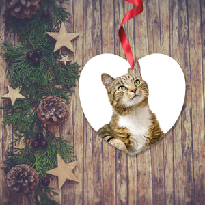 Dark wooden background with a Christmas Garland stretched out on the Left hand side from top to bottom. On the garland are some wooden stars and fir cones along with some dark red berries. To the right of the garland is a Christmas Decoration in the shape of a heart with a red ribbon. The decoration is is a picture of a tabby cat with a white background. Decoration as supplied by Photogifts.co.uk