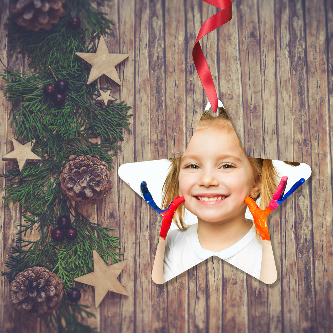 Dark wooden background with a Christmas Garland stretched out on the Left hand side from top to bottom. On the garland are some wooden stars and fir cones along with some dark red berries. To the right of the garland is a Christmas Decoration in the shape of a star with a red ribbon. The decoration is is a picture of a girl holding up her hands with each finger covered in a different colour paint as if she is about to do some hand painting.. Decoration as supplied by Photogifts.co.uk