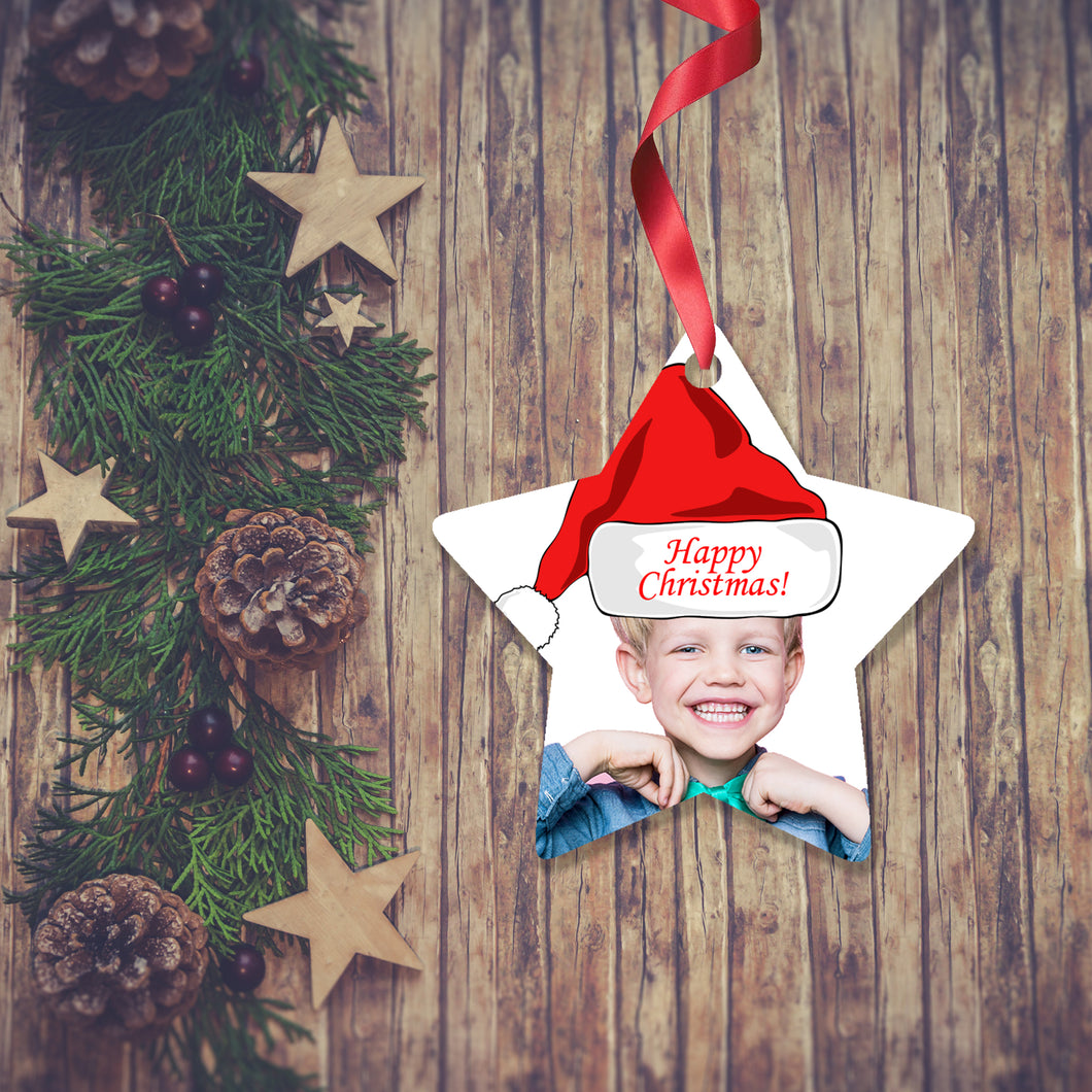 Dark wooden background with a Christmas Garland stretched out on the Left hand side from top to bottom. On the garland are some wooden stars and fir cones along with some dark red berries. To the right of the garland is a Christmas Decoration in the shape of a star with a red ribbon. The decoration is a picture of a boy's head and shoulders with a santa hat saying Merry Christmas. Decoration as supplied by Photogifts.co.uk