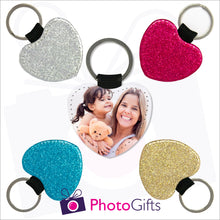 Load image into Gallery viewer, Four glitter heart shaped keyrings surrounding a photo heart shaped keyring. Each of the glitter keyrings is a single coloured glitter in either red, blue, silver or gold. The central keyring shows the face of a mother holding a toddler and teddy bear. Also shown is the Photogifts logo. Keyring as produced by Photogifts.co.uk