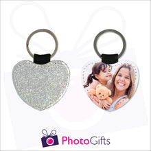 Load image into Gallery viewer, Front and back image of a heart shaped keyring. On one side the heart is all silver glitter and on the other is a photo of a mother holding a toddler and teddy bear in her arms. There is also the Photogifts Logo. Keyring as produced by Photogifts.co.uk