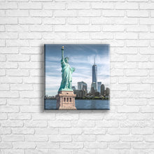 "Load image into Gallery viewer, Personalised 12x12"" square wrapped canvas with your own choice of image hung on a white brick wall by Photogifts.co.uk"