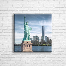 "Load image into Gallery viewer, Personalised 16x16"" square wrapped canvas with your own choice of image hung on a white brick wall by Photogifts.co.uk"