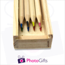 Load image into Gallery viewer, Close up of small wooden personalised pencil case showing slot where the top slides in and the 8 pencils that come with the box as produced by Photogifts.co.uk