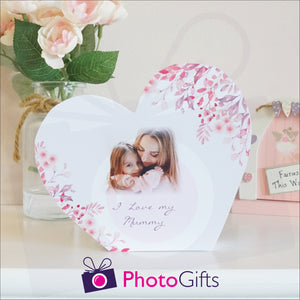 "White wooden block in the shape of heart with the personalised photo of a mother and child with the words ""I Love you mummy"" and some flowers on a white shelf as supplied by Photogifts.co.uk"