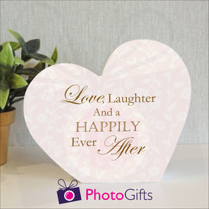 "White wooden block in the shape of a heart with the slogan ""Love, laughter and a happily ever after"" printed on the block. The block and a potted plant is on a white shelf. Personalised block as supplied by Photogifts.co.uk"