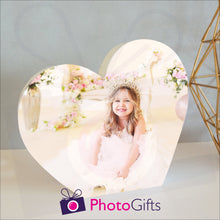 Load image into Gallery viewer, White wooden heart shaped block with a picture of a girl in a tiara and white dress sitting surrounded by flowers. White block and personalised photo as supplied by Photogifts.co.uk