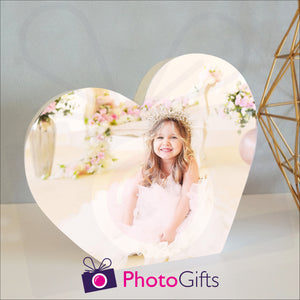 White wooden heart shaped block with a picture of a girl in a tiara and white dress sitting surrounded by flowers. White block and personalised photo as supplied by Photogifts.co.uk