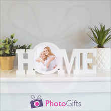 "Load image into Gallery viewer, ""Home"" in a white painted wooden block with a picture of a mother and daughter having fun in stuck in the middle of the ""O"" of the home word. Shown on a white shelf with a couple of potted plants either side. Wooden word ""Home"" and personalised photo as supplied by Photogifts.co.uk"