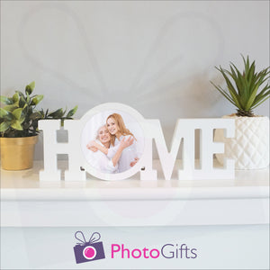 """Home"" in a white painted wooden block with a picture of a mother and daughter having fun in stuck in the middle of the ""O"" of the home word. Shown on a white shelf with a couple of potted plants either side. Wooden word ""Home"" and personalised photo as supplied by Photogifts.co.uk"