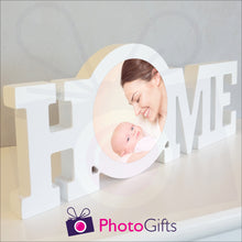 "Load image into Gallery viewer, ""Home"" in a white painted wooden block with a picture of a mother and baby having fun stuck in the middle of the ""O"" of the home word. Shown on a white shelf as supplied by Photogifts.co.uk"