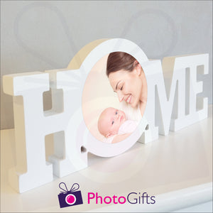 """Home"" in a white painted wooden block with a picture of a mother and baby having fun stuck in the middle of the ""O"" of the home word. Shown on a white shelf as supplied by Photogifts.co.uk"