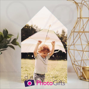 White wooden block in the outline of a house with a personalised photo of a boy and his kite attached to the block on a white shelf with a plant and a candle holder on either side. Block and personalised photo as supplied by Photogifts.co.uk