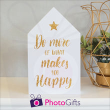 "Load image into Gallery viewer, White wooden block in the shape of a house with the slogan ""Do more of what makes you happy"" printed on the front. The block is resting on a white shelf with a potted plant to one side. Personalised block as supplied by Photogifts.co.uk"