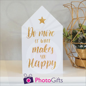 "White wooden block in the shape of a house with the slogan ""Do more of what makes you happy"" printed on the front. The block is resting on a white shelf with a potted plant to one side. Personalised block as supplied by Photogifts.co.uk"