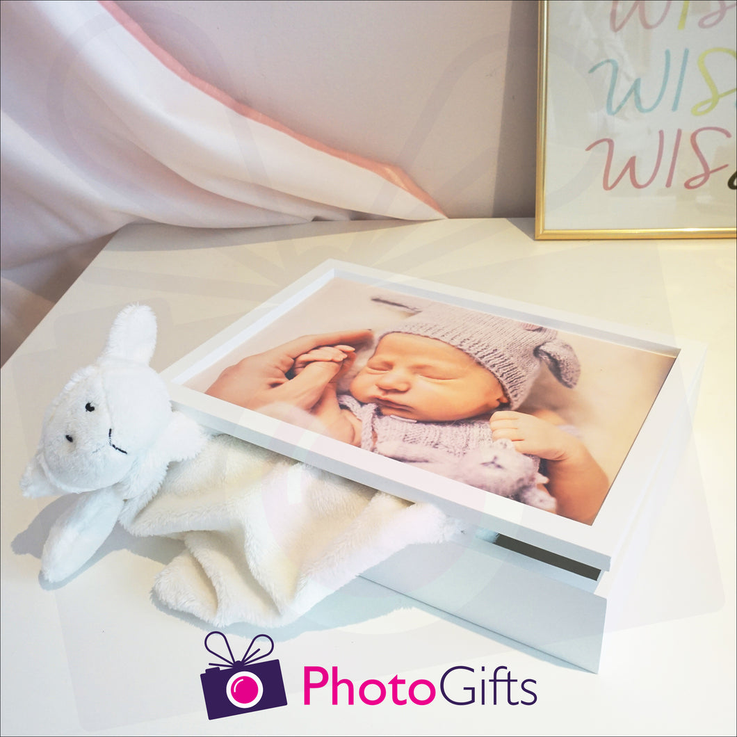 White wooden keepsake box that has been personalised with a baby's photo holding on to a parents hand. Box is slightly open with a soft toy partially in the box. The box is sitting on a white shelf with a curtain and picture in the background. Personalised box as supplied by Photogifts.co.uk