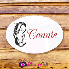 "Load image into Gallery viewer, Oval metal outdoor sign on a wooden background. Within the oval panel is a picture of a horses head and to the right is the word ""Connie"" in red text. All as produced by Photogifts.co.uk"