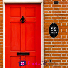 Load image into Gallery viewer, Red brick house with a close up of the red front door with black in door letterbox and knocker. To the right of the door as you face the door is a black oval panel with the number 82 and the word Smith printed on the panel along with some scroll work in the background. Panel as produced by Photogifts.co.uk