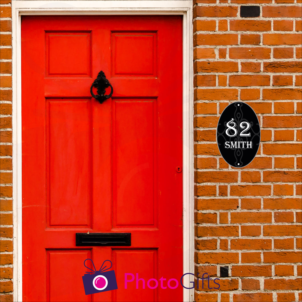 Red brick house with a close up of the red front door with black in door letterbox and knocker. To the right of the door as you face the door is a black oval panel with the number 82 and the word Smith printed on the panel along with some scroll work in the background. Panel as produced by Photogifts.co.uk