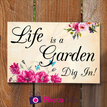 "Load image into Gallery viewer, Rectangular panel in landscape orientation on a wooden fence. On the panel is the slogan ""Life is a garden Dig In!"" together with pictures of some vibrant flowers and some bright blue butterflies. As produced by Photogifts.co.uk"