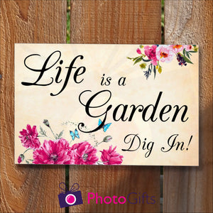 "Rectangular panel in landscape orientation on a wooden fence. On the panel is the slogan ""Life is a garden Dig In!"" together with pictures of some vibrant flowers and some bright blue butterflies. As produced by Photogifts.co.uk"