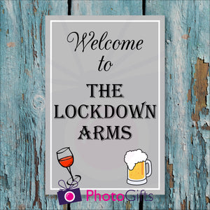 "Light blue but worn painted wooden fence with a panel attached to the fence. On the panel is the wording ""Welcome to The Lockdown Arms"" and a picture of a wine glass and beer tankard. As produced by Photogifts.co.uk"