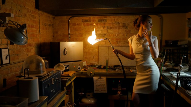 Woman in a white dress holding a blowtorch