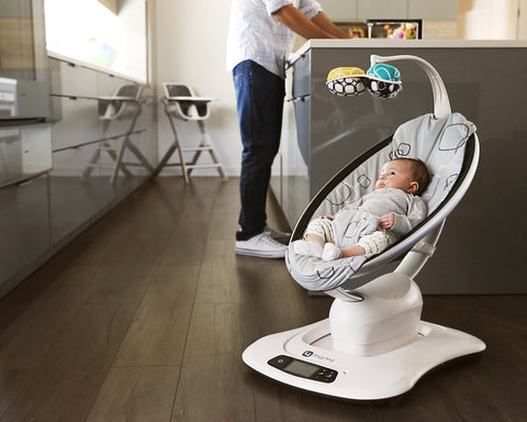 Baby in an electric baby swing while dad cooks