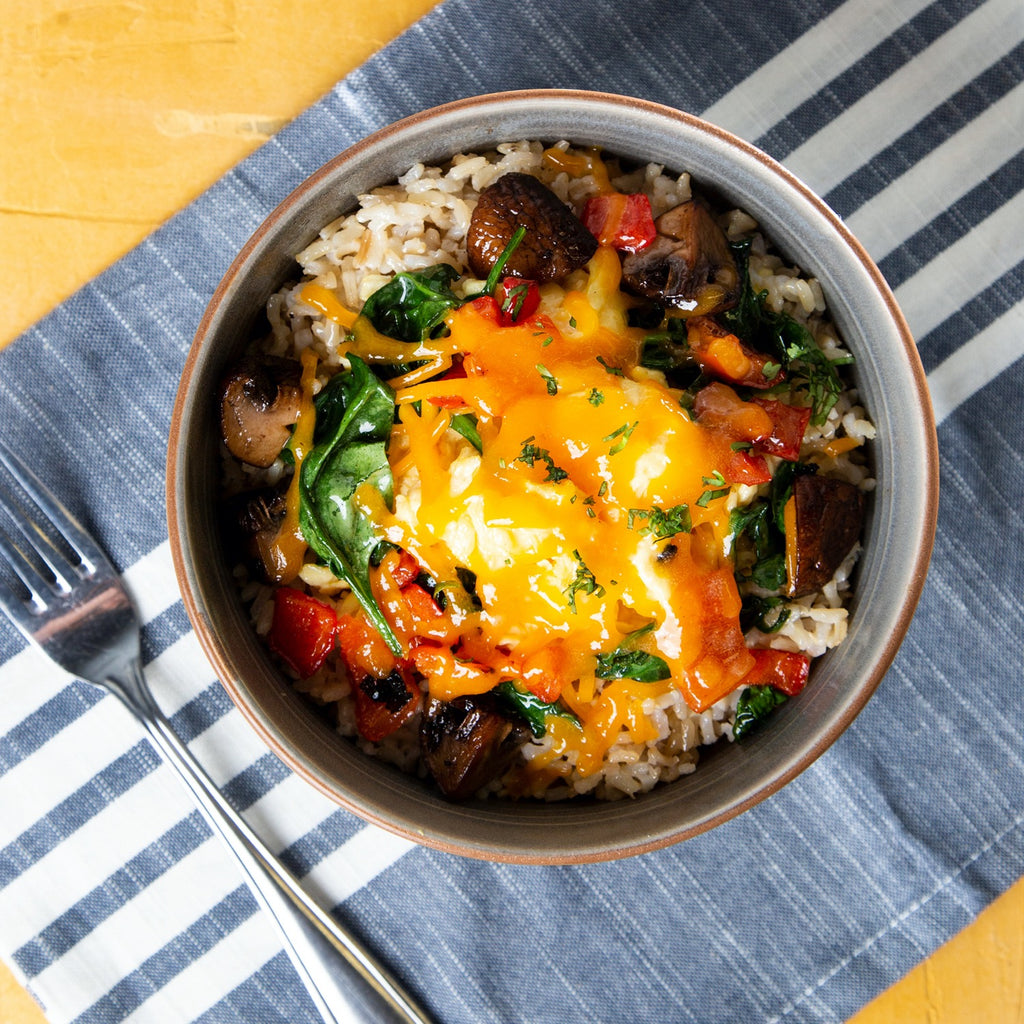 Hearty Breakfast Bowl with rice, fresh scrambled eggs, spinach, mushrooms and red peppers.