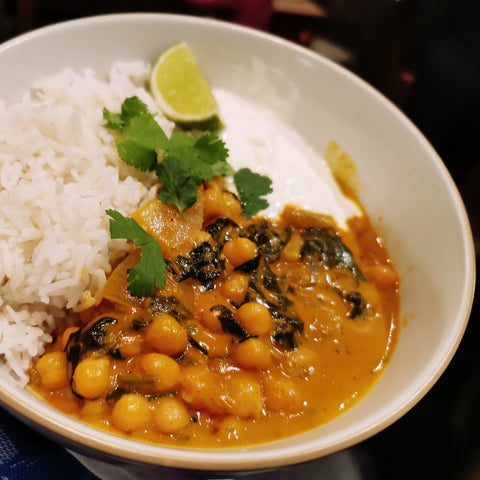 Chickpea curry with vegetables and basmati rice, served in a white bowl with a lime wedge and fresh coriander leaves