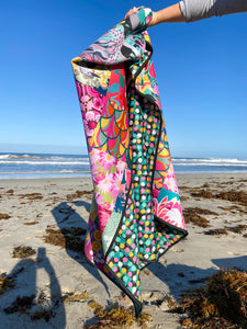 A person is holding a neoprene picnic blanket to display both the patchwork Pink Lake Road original Pink Wattle design, and the reverse side of a spotty pink, yellow, green and cream pattern