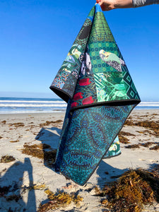 A person is holding a neoprene picnic blanket to display both the patchwork Pink Lake Road original Emerald Boab design, and the reverse side of a blue, black and green lined mirror pattern