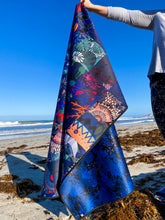 Load image into Gallery viewer, A person is holding a neoprene picnic blanket to display both the patchwork Pink Lake Road original Blue Dhufish design, and the reverse side of a blue and black coral and sea flora pattern