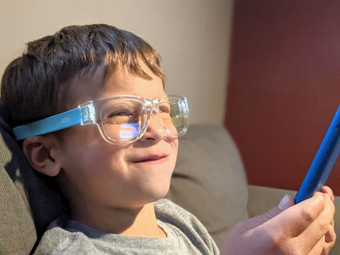 Boy browses iPad while wearing blue blocking snappies glasses