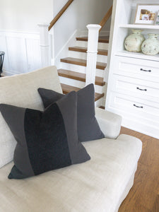 This is a photo of a modern farmhouse / hamptons coastal / restoration hardware style throw pillow.  The colours are black and charcoal.  The fabric consists of mohair fur and 100% belgian linen.  It is styled on a linen love seat sofa.