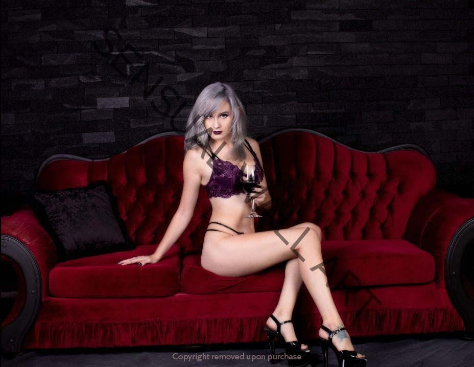 young lady with silvery hair in lingerie on red couch holding wine glass