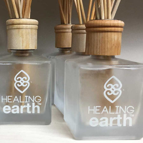 Healing earth glass bottle with rattan diffuser reeds and wooden cap available at SR Amenities Hotel and Spa Supplies.
