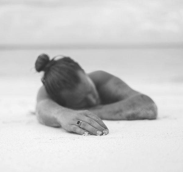 man laying on beach with manicure hand forward