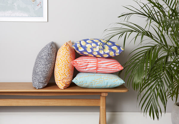 colourful cushions stacked on a bench next to a plant