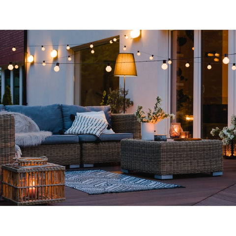 a grand patio with decent furnitures and cozy lighting with string lights, lanterns, and candles