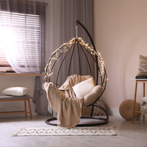 A chair with string lights in a living space with elegant interior design