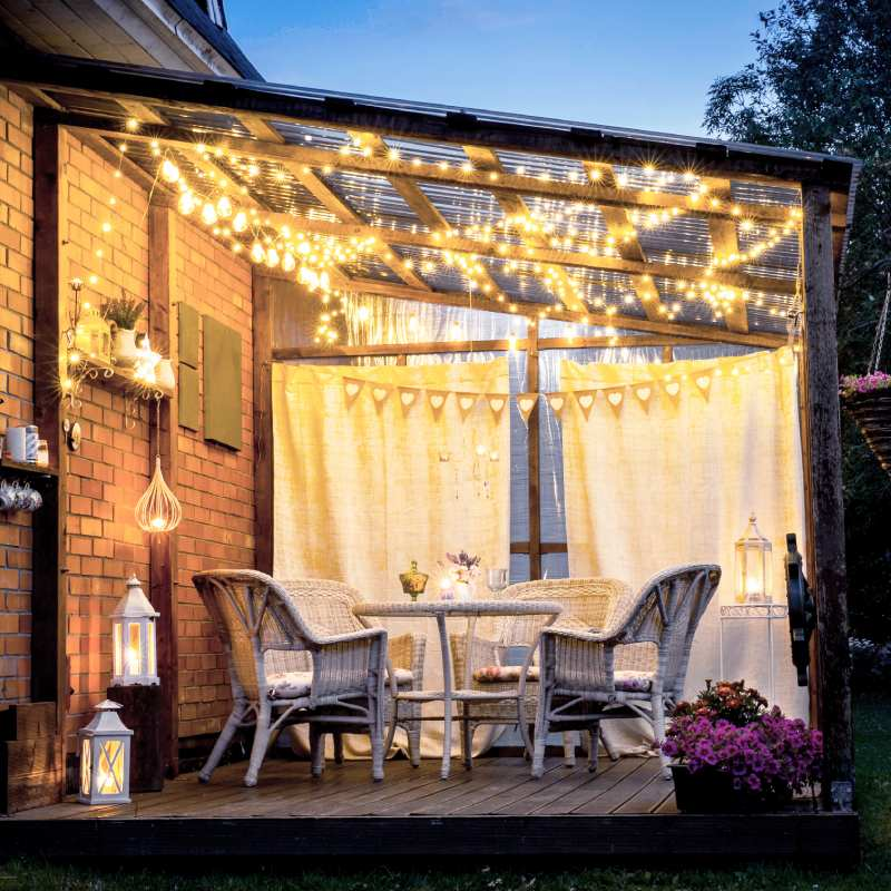 Starlit Gold LED String Lights being strung in the pergola in the patio area of garden