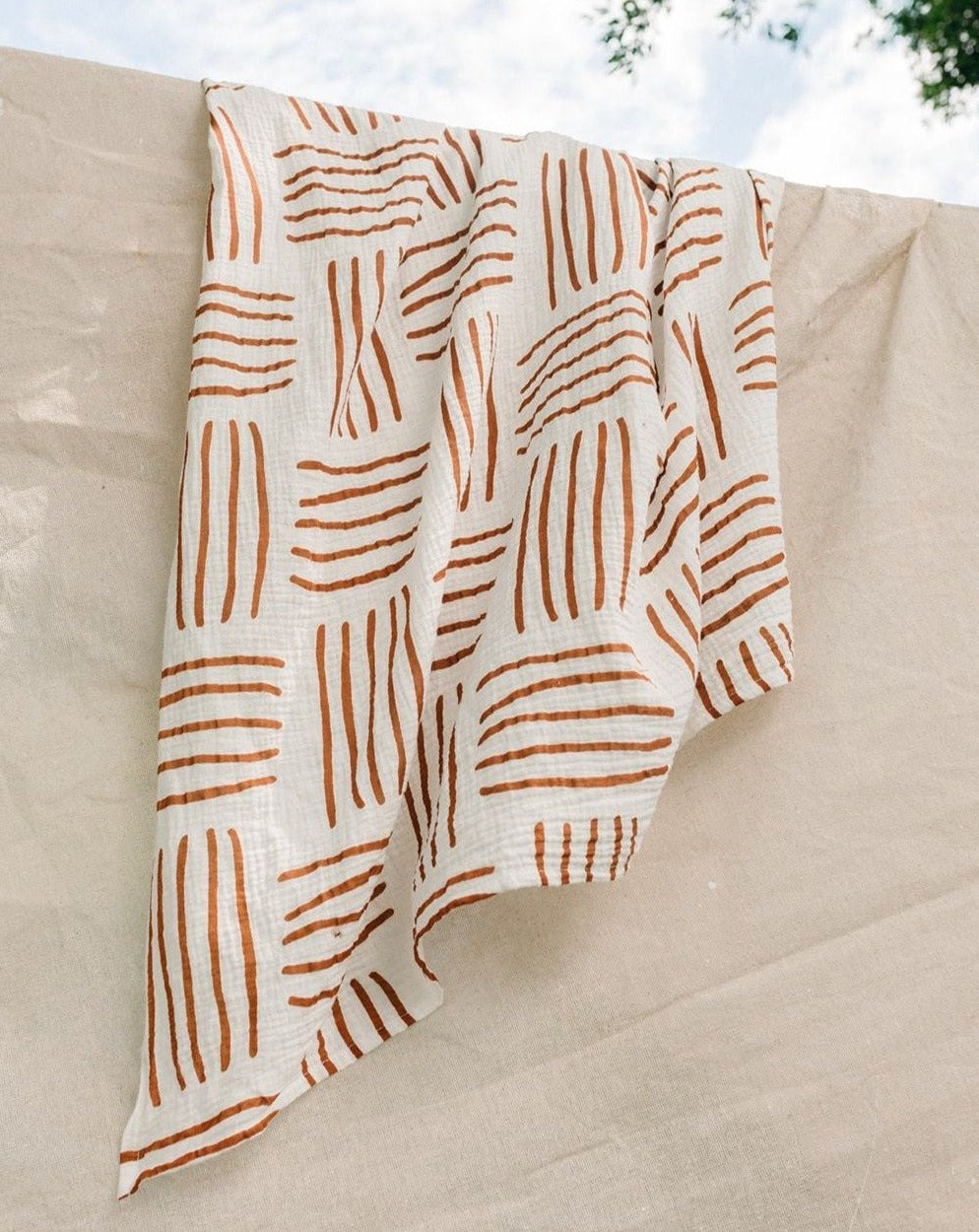 stunningly soft and durable earth wrap with Taninaka's Horizon print. New release design in organic cotton muslin this swaddle has brunt orange horizontal and vertical lines on a white or off white cotton background