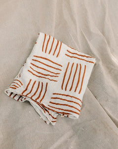 horizon print organic muslin wraps by Taninaka - Stunningly soft and durable baby swaddle with burnt orange print on white organic cotton muslin