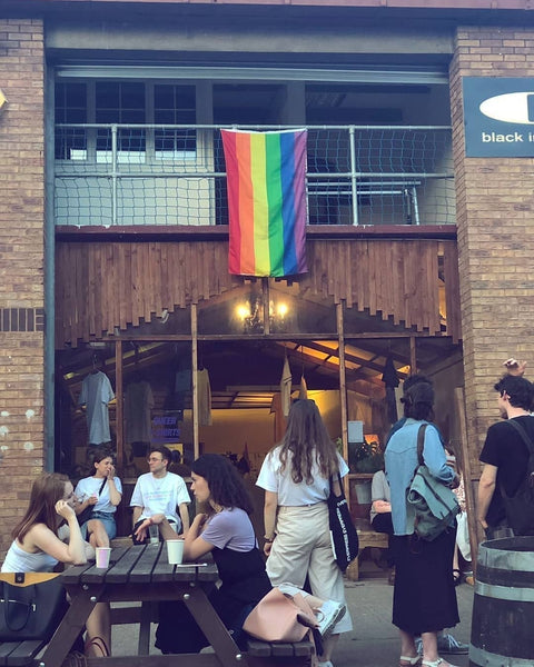Exterior of the Queer T-Shirts exhibition with a Pride flag draped above the entrance