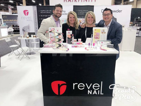 four people standing at trade show booth