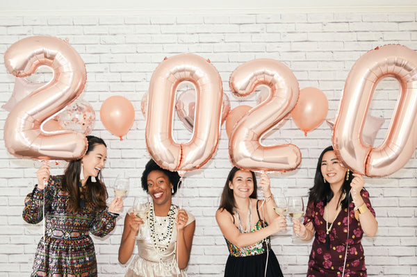 "four women holding ""2020"" new year balloons signifying flying time and the new year as part of K-beauty influenced holistic skincare habits and rituals"