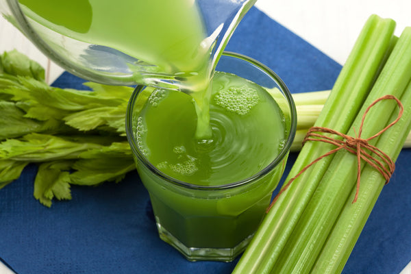 celery juice being poured from a pitcher into a glass cup with celery stalks displayed around it symbolizing the importance of celery juice boosted good digestion for glowing skin as part of K-beauty inspired holistic skincare habits and rituals