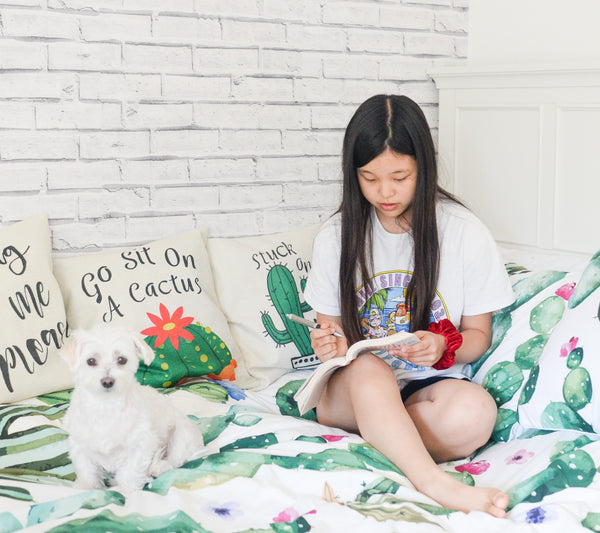 young girl reading in cactus themed bed with small white dog symbolizing the importance of developing K-beauty influenced holistic skincare habits early