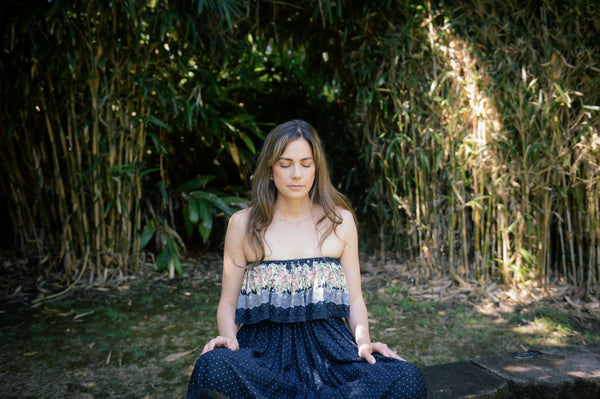 beautiful woman with glowing skin and eyes closed meditating in bamboo forest on a silent meditation retreat for holistic skincare